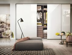 Lema's wardrobe with glossy lacquer sliding doors, with internal equipment that can be outfitted to match your lifestyle. Our wardrobes can be freestanding, with finished sides or, as pictured, surrounded by sheet-rock for a built-in look. For design lovers who want to add a little bit of luxury and glamour to their morning routine.