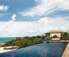 """""""I wondered, How can I bring Bali three and a half hours away?"""" says fashion designer Donna Karan, who envisioned a simple, modern beach house on Parrot Cay, in the Turks and Caicos Islands. (With Local Materials and Tropical Detailing, the Fashion Designer DONNA KARAN Dreams Up a Family Retreat in the British West Indies)"""