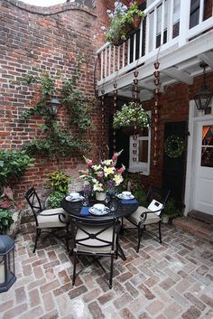 """""""The design takes advantage of the double height space by using a repeated element, Smith & Hawken Copper Rain Chains, along the length of the balustrade. A petite, traditional dining set, Smith & Hawken Allogio Collection, complements the traditional brick and New Orleans details found throughout the courtyard. The additions are selective and tasteful in order to highlight the great inherent qualities of the courtyard."""""""