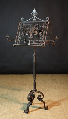 An 18th Century French Wrought Iron Lectern. The apex top ornamented with fleur-de-lis and scrollwork and having two retractable pricket arms. Raised on a tripod base. 65 ins (165 cms) high, 20 ins (51 cms) wide, 18½ ins (47 cms) deep.