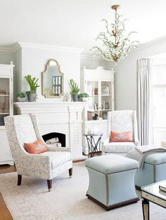 "This powder-blue living room is from Better Homes & Gardens. Here's how they describe it: ""Colors don't need to be bright or bold to make a big impact in a space. In this room, powder blue walls and a white fireplace make a pleasant pair. Identical straight-back chairs and ottomans pull color from the walls, while decorative rosy pink pillows add a touch of warmth. For a little shine, choose a bejeweled chandelier to complete an elegant look."""