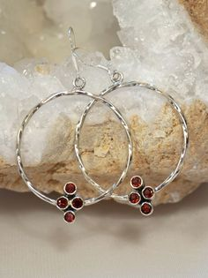"Each handmade sterling hoop earring has a cluster of 4 sparkling faceted Garnet gemstones, each bezel-set in 925-hallmarked sterling silver. Earring circumference: 1.35"" Total earring length: 2"""