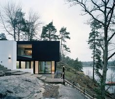 Perched on a rocky slope between pines with a waterway at its feet, Casa Barone is an ultra-modern hillside house designed by Sweden architects WRB. In sharp contrast to its more traditional neighbors, this contemporary Swedish house plan features a flat roof and a minimalist black exterior framing its massive windows //
