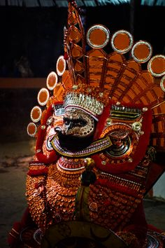 A dancer in Theyyam costume, a traditional ritual art form native to northern Kerala, India.