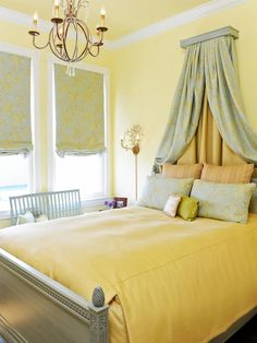 """Pink isn't the only choice for a bedroom fit for a princess: Yellow is an unexpected, but undeniably rich option as well. """"This south-facing bedroom called out for washing the walls in buttery yellow,"""" says designer Brian Dittmar. """"The result is a room that just makes you feel happy. The Swedish-style bed — complete with a corona — plus an aged gold chandelier with crystal accents and pops of pale blue, green and pink give this space a decidedly traditional, but very warm and welcoming…"""
