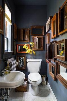 Mit holzgerahmten Spiegeln auf graublauer Wand wirkt das Gäste-WC edel und urig zugleich.
