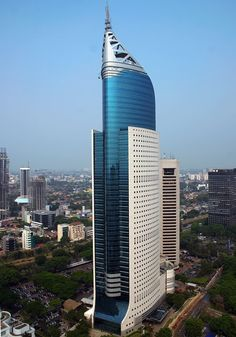 """bautyofworld:"""" Wisma Indonesia Wisma 46 is a 262 m tall (architectural height) skyscraper located in the Kota BNI-Maybank complex at Jalan Jenderal Sudirman in Central Jakarta, Indonesia. The 48 storey office tower was completed in 1996 under. Modern Architecture Design, Facade Design, Futuristic Architecture, Beautiful Architecture, Chinese Architecture, Future Buildings, Unique Buildings, Amazing Buildings, Building Facade"""