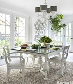 """This Kansas City house's dining room, a former loggia, is """"light, bright, and airy,"""" homeowner and designer Zim Loy says. """"I accomplished that with lots of white paint."""" She bought a beat-up old $60 table at an estate sale and gave it a fresh new look by the painting the base high-gloss white. Its curves echo the arms of the Barbara Cosgrove chandelier. Pin it now. See more quick home decorating ideas.    - HouseBeautiful.com"""