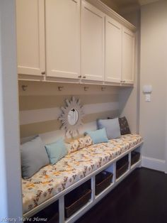 cheery mudroom....like the long bench with baskets on the bottom.  Fabric and pillows kinda cute.