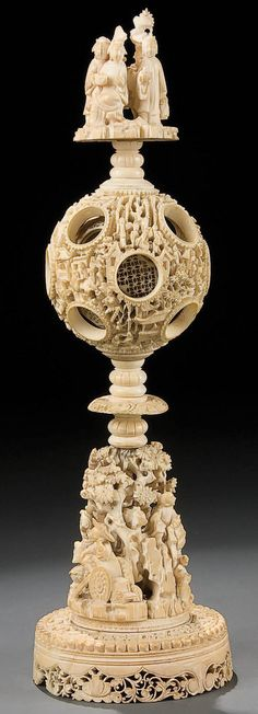 AN ORIENTAL CARVED IVORY PUZZLE OR MYSTERY BALL early 20th century with a carved figural garden scene pedestal supporting a carved puzzle ball comprising. approximately 14 graduating layers below a figural carved finial.