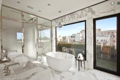 This light-filled bathroom on Jane Street, NYC has marble floors, marble walls, marble counters, a glass enclosed shower room, dual sinks, a stand-alone oval tub, and a wall of glass overlooking the balcony.