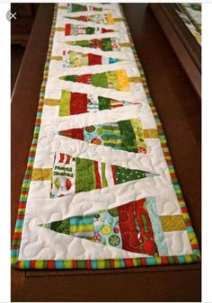 This table runner measures 71 inches long by 11 inches wide. I used Ho Ho Ho Let it Snow fabric with two layers of warm and natural batting to maintain shape. The backing is a coordinating christmas fabric. Christmas Abbott, Christmas Tree On Table, Christmas Tree Quilt, Christmas Patchwork, Christmas Runner, Christmas Placemats, Christmas Fabric, Christmas Crafts, Christmas Ornaments