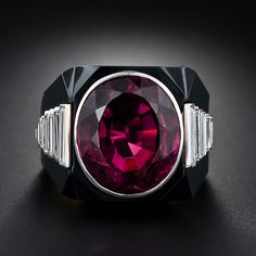 On a grand scale, this fabulous ring showcases a deep raspberry-red oval-shaped rubelite tourmaline weighing 13.00 cts. Expertly cut black onyx plaques create a framework for the gem with a streamlined row of graduated, shimmering, baguette-cut diamonds running down the ring's sculpted shoulders. A bold and dramatic, masterfully crafted one-of-a-kind work of jewelry art. Total diamond weight: 1.50 carats.