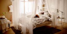 Bild av sovrum med huvudgavel gjord med svart och vit textiltejp TUVBRÄCKA påslakan i svartvitt. Orange STOCKHOLM kudde.
