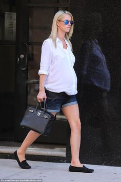 Maternity style:Nicky looked at ease while strolling through the Soho neighborhood in a preppy chic ensemble of denim shorts and a button down tunic