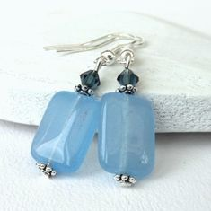 Beautiful pastel blue chalcedony rectangles are contrasted with lovely deeper blue crystal elements by Swarovski® Little silver coloured -daisy- shaped beads separate the gemstone and crystal. The earrings hang from silver plated earwires, which can be. Jewelry Gifts, Jewelery, Handcrafted Jewelry, Handmade, Blue Chalcedony, Organza Gift Bags, Pastel Blue, Blue Crystals, Small Gifts