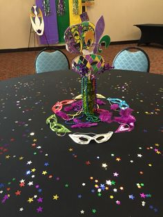 Mardi Gras Centerpieces with mask cutouts and beads and emblems.