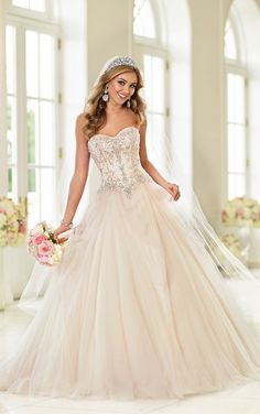 Beautiful Layers of tulle and organza make up the flowing skirt of this ballgown wedding dress. Diamante encrusted delicate beading pattern adorn the sweetheart bodice. Available zipper or lace-up back.