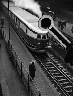 Man on a train platform next to the the train Hamburg Flyer (or Flying Hamburger, German: Fliegender Hamburger) on its first voyage from the Lehrter Bahnhof in Berlin to the main train station in Hamburg, Germany. Photo, 1932.