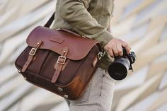 Our St. James's Street camera bag is modeled off of the revered English field bag. We pair brown bubble leather with triple layered canvas. Made in England. Thick Leather, Tan Leather, Leather Camera Bag, Prime Lens, Metal Bar, Camera Gear, Cheap Bags, England, Pairs