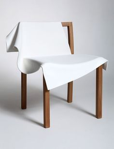 """Toga Chair"" by Reut Rosenberg - photo from chairblog (6/04/13);   This ""consists of a simple European oak frame and PVC sheet, formed in a mould. The plastic not only acts as a visual expression of cloth, but also a practical, constructive component to replace the frame's back link and seat, providing minimalist comfort."""