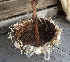 I love this darling rustic flower girl basket! The weaving of twine and vines make it a unique little basket for a rustic country or barn wedding.  This basket is oval and I added specially preserved babys breath by me all the way around the rim. The preserved babys breath is soft and pliable and wont break off. I added 6 mini sola flowers mixed in and a sheer ribbon at the base of each side of the handle. Measurements ~ 12 tall to the top of the handle, 8 x 7 and 4 deep.  ***Please note…
