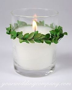Classic white votive candle with a boxwood garland accent. http://www.yourweddingcompany.com #candleideas
