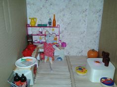 Het muizenhuis (zelf gemaakt). De keuken met Julia. Spullen zijn kosteloos materiaal, spullen van Barbie/Lego etc., maar ook andere spullen: de borden zijn theezakschaaltjes, het tafeltje is een omgedraaid houten doosje, de krukjes zijn de dekseltjes van een tandenverzameldoosje etc.