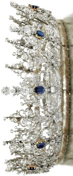 """This tiara... dates to the early 1900s is designed as a series of thirteen graduated stylized ribbon and scroll elements. The ribbons and scrolls are set with circular-, single-cut, cushion-shaped and oval diamonds and each highlighted in the center with an oval sapphire."""