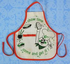 """This hard to find apron is part of Ken's Pak """"Cheerful Chef"""", issued in 1964. The apron is made of white linen and printed in green and black. The apron is trimmed in red and has a red elastic strip that is used to hold/hang the chef's utensils (utensils not included). 