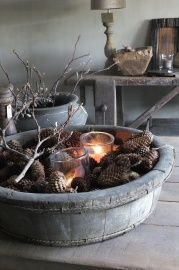 Rustic table decor with pine cones, candles and branches.