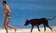 Shah of Iran and one of his doberman pinchers at the beach