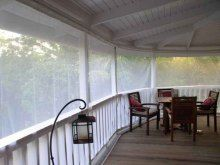 Mosquito curtains for porch that are retractable.  White version from the inside.