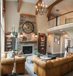 Soaring Two Story Family Room with very large wall clock.  Love the clock and the lanterns on the fireplace