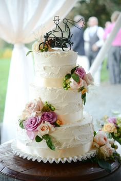 White floral wedding cake with an iron topper (Photo by Larsen's Photography)