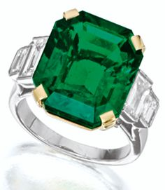 EMERALD AND DIAMOND RING.       Centring on a step-cut emerald weighing 10.12 carats, flanked on each side by two baguette diamonds together weighing approximately 1.00 carats, mounted in platinum and 18 karat yellow gold. Sotheby's.