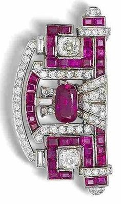 An art deco ruby and diamond plaque brooch, circa 1930. The central cushion-shaped mixed-cut ruby, weighing 2.18 carats, between two cushion-shaped diamonds, within a pierced scroll-shaped mount, symmetrically-set with calibré-cut rubies and brilliant, old brilliant, single and baguette-cut diamonds, diamonds approximately 3.15 carats total, length 5.2cm.