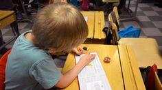 Ala-koululainen kirjoittaa pulpetissaan vihkoon.