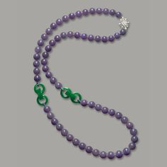 Lavender Jadeite bead and Jadeite triple hoop necklace.  Composed of sixty-three graduated translucent lavender jadeite beads, highlighted by two jadeite triple-hoops of translucent emerald green colour, completed by a clasp set with oval and brilliant-cut diamonds together weighing approximately 1.80 carats, mounted in 18 karat white gold, length approximately 830mm.