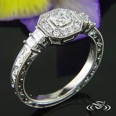 Antique Custom Design diamond halo ring for Asscher cut diamond with basket set baguettes on the side and scroll engraving with miligrain edges.