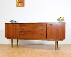 Long and Low Sleek Teak Danish Inspired Credenza/Buffet/ TV Console by Nathan with original labelCirca 1960\'sA beautiful, sleek piece with Danish inspired design and beautiful wood grain.Beautiful leg detail and integrated handles.Featuring 3 Center Drawers with the top drawer having a divider and lined with green felt.2 doors either end with shelving - lots of storage.B