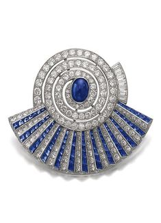 An Art Deco sapphire and diamond brooch, 1930s. Designed as a stylised éventail, set with a cabochon and calibré-cut sapphires, circular-, single-cut and baguette diamonds.