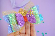This beautiful piece is the perfect Little mermaid Princess Bow for the lil princess. Perfect to accent your Disney outfit. Bow is available in 2 different sizes {picture Large Bow 4 inches approx.} and can be attached to a 1/4 elastic headband, nylon elastic or Clip . If you select