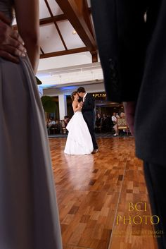 A unique low angle shot between the legs of the bridal party as they look on as our the bride and groom enjoy their first dance as husband and wife following their wedding ceremony at Harbour Ridge Yacht and Country Club in Pt St Lucie Florida.