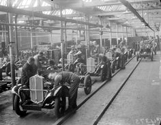 A photograph showing the manufacture of Triumph cars at Triumph works, Coventry, taken in September 1933 by Leslie Cardew for the Daily Herald.    The photograph shows workers stationed in rows at intervals, assembling the chassis and engine on the assembly line. The first Triumph motor car, the model 10/20, was manufactured by the Triumph Cycle Company in Coventry in 1923 . The last, the saloon car Triumph Acclaim, rolled off the British Leyland assembly line in 1984.