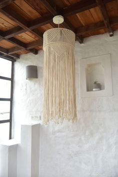 This macramé lamp, inspired by old latticed doors, is painstakingly woven by rural artisans of India. Its intricately woven pattern adds warmth and character to indoor spaces.
