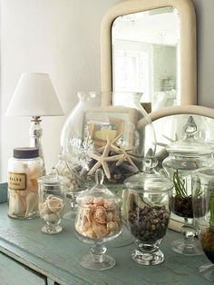 Old apothecary and candy jars display a collection of seashells and river rocks. Placing a trio of mirrors behind the display amplifies its impact.