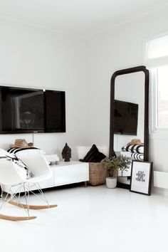 black + white details... love the low, white cabinet + oversized black mirror leaning against the wall
