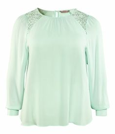 Blouse in chiffon and lace. Gathers on shoulders, wide neckline, and covered buttons at back of neck and cuffs. In Mint Green