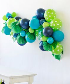 Transport your guests to the dinosaur jungle with this blue and green balloon wall garland. Mix different balloons and large faux leaves to create depth. T-Rex/Dinosaur Party styling by Happy Wish Company. Photography by Tammy Hughes Photography. Stationery by Minted artist, Patricia Wallace.
